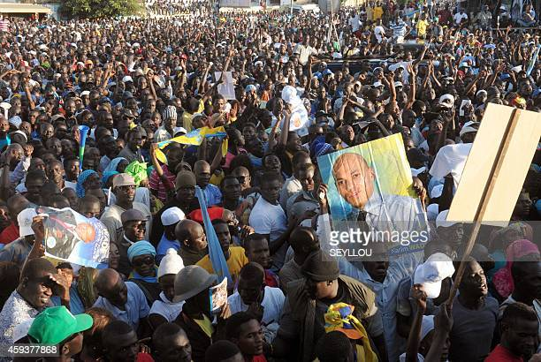 Opposition supporters hold up placards as they rally in the Senegalese capital Dakar on November 21 as the former president of Senegal Abdoulaye Wade...