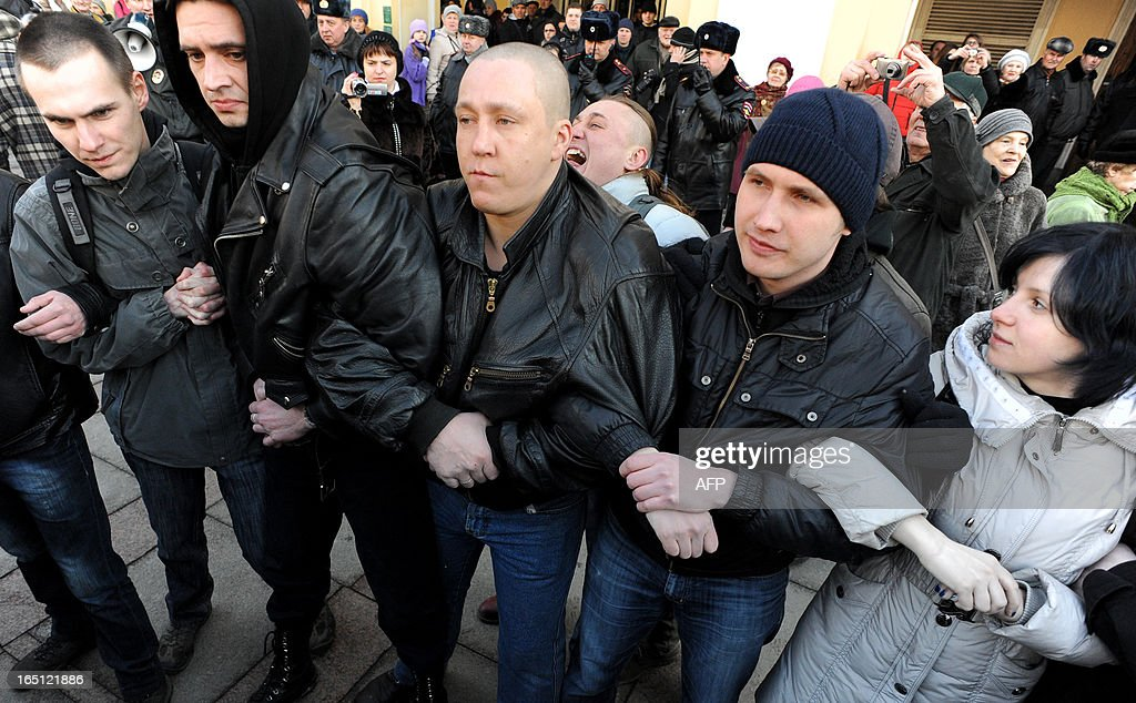 Opposition supporters interlace their arms in central St. Petersburg on March 31, 2013, during an unauthorized protest rally to defend the article 31 of the Russian constitution which guarantees freedom of assembly. Russian opposition activists call on authorities to respect the right to organize rallies every 31st of a month, which often leads to arrests by the police.