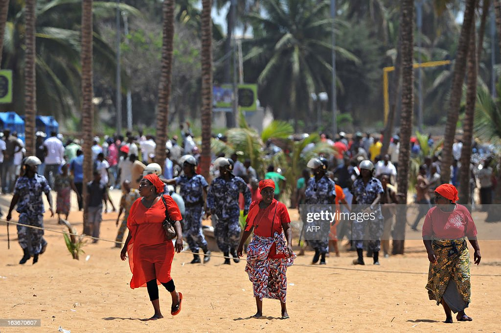 Opposition supporters run across the beach as police evacuate demonstrators who attempted to hold a sit-in near the Presidency in Lome on March 14, 2013 to protest a law which has given the HAAC (Haute Autorite de l'Audiovisuelle et de la Communication) more power. The protesters were forced away from the Presidency by security forces and several journalists were reportedly injured by tear gas and rubber bullets. AFP PHOTO / Daniel Hayduk