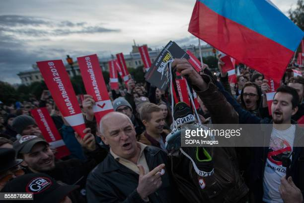 Opposition supporters seen holding placards and the Russian flag while participating in an unauthorized rally The President of Russia Vladimir Putin...