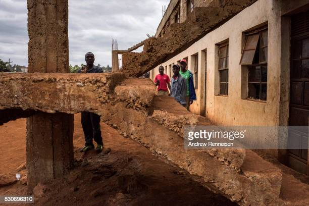 Opposition supporters take cover from Kenyan police forces in the Kibera slum on August 12 2017 in Nairobi Kenya Demonstrations turned violent in...