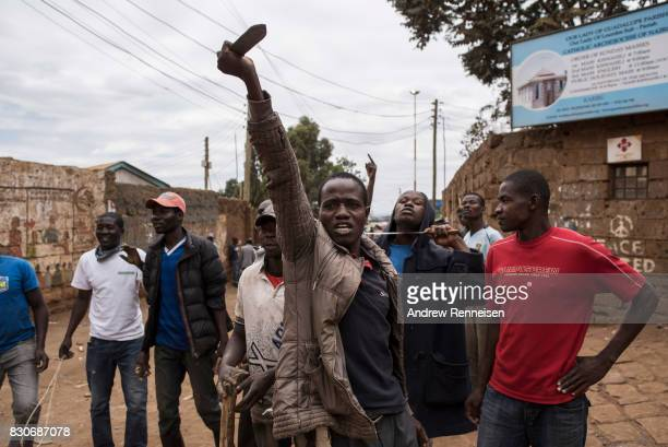 Opposition supporters taunt Kenyan police forces as the two sides clashed in the in the Kibera slum on August 12 2017 in Nairobi Kenya Demonstrations...