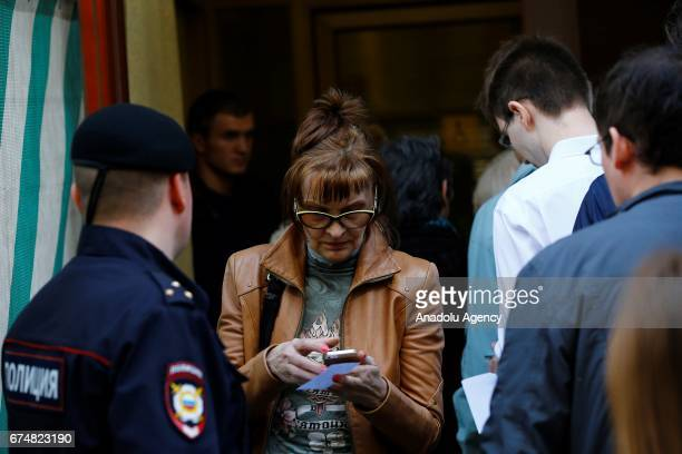 Opposition supporters wait in queue outside the president's administrative office to deliver letters calling for Vladimir Putin not to stand for a...