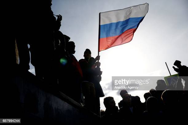 Opposition supporters wave a Russian flag during an opposition rally on March 26 2017 in Moscow