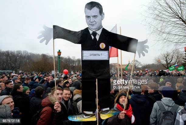 TOPSHOT Opposition supporters with a cutout figure depicting Prime Minister Dmitry Medvedev participate in an anticorruption rally in central Saint...