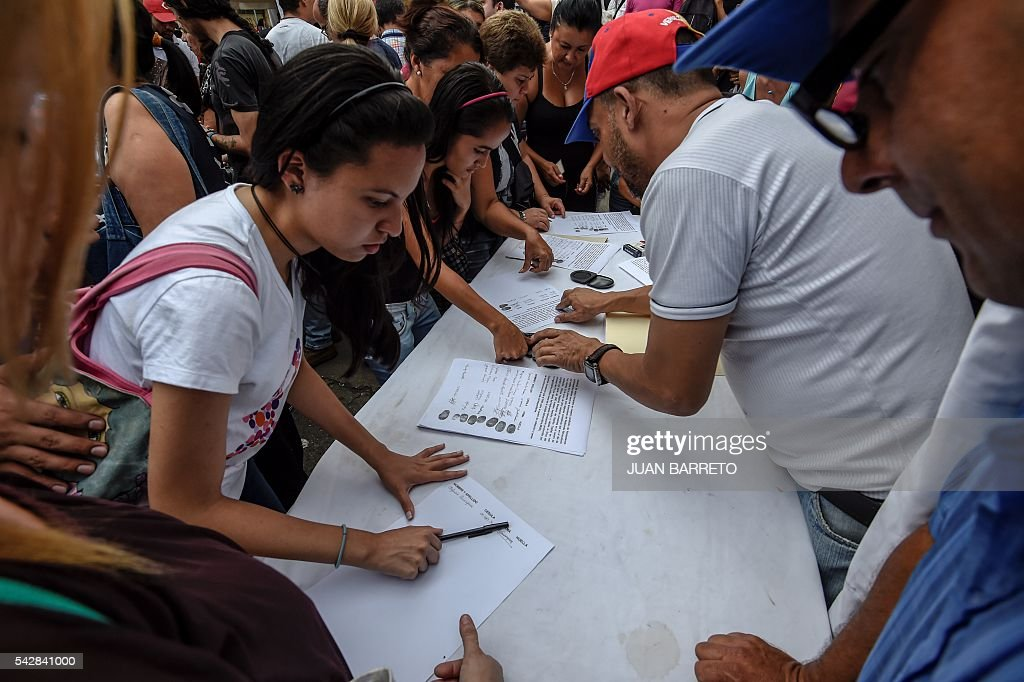 Oppositors of Venezuelan president Nicolas Maduro authenticate their signatures for a recall referendum in front of the National Electoral Council (CNE) in Caracas, on June 24, 2016. Soaring crime, runaway inflation and a sharply contracting economy, worsened by falling oil prices, have fueled a drive for a recall referendum to remove Maduro, as a way out of the crisis. / AFP / Juan BARRETO
