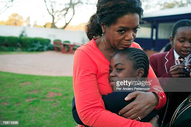 Oprah Winfrey hugs one of the girls that she interviewed for her school for unprivileged girls on August 10 2006 in Johannesburg South Africa Oprah...