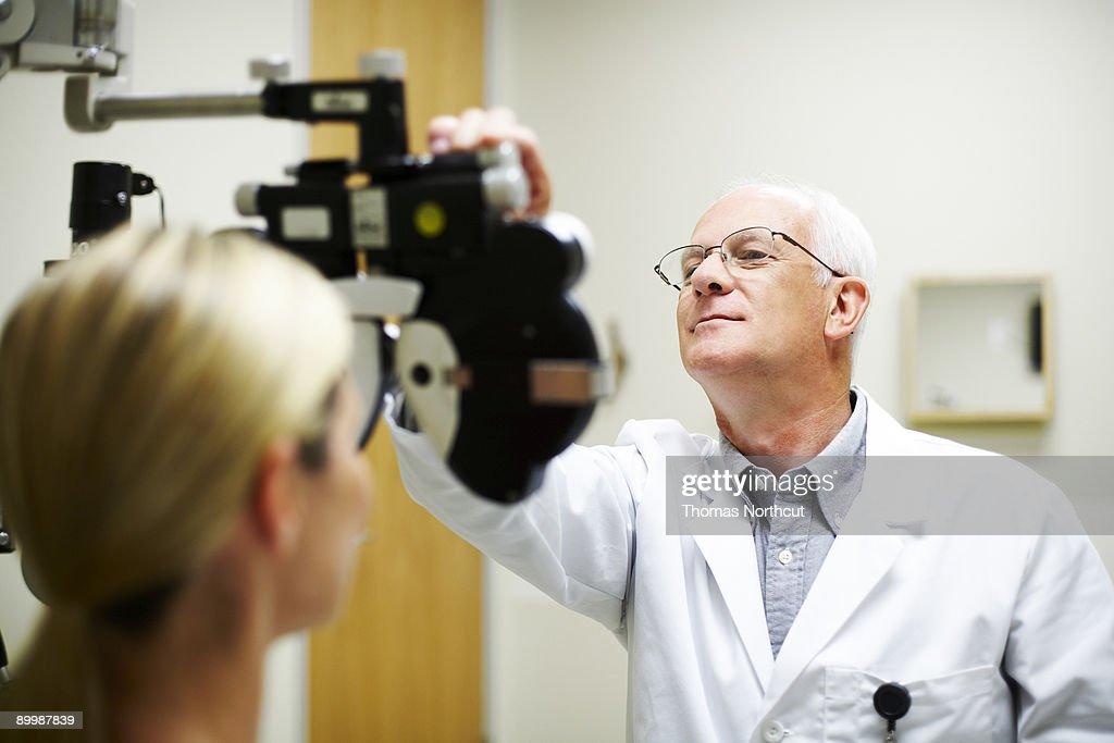 Opthamologist measuring patient's eyesight : Stock Photo