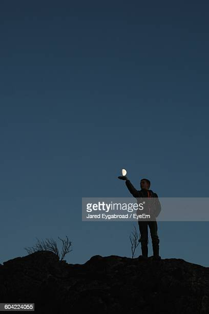 Optical Illusion Of Boy Holding Moon At Dusk