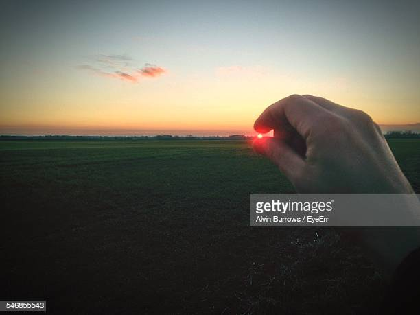 Optical Illusion Of Hand Holding Sun Over Field During Sunset