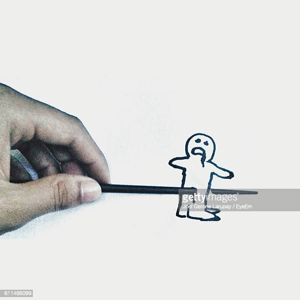 Optical Illusion Of Hand Stabbing Character On White Paper