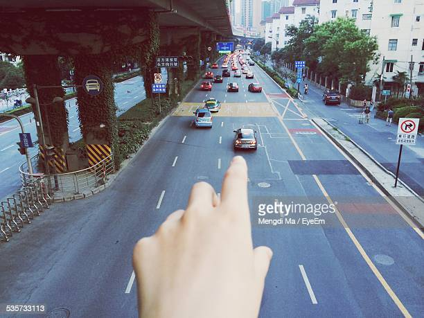 Optical Illusion Of Hand Touching Car On Road