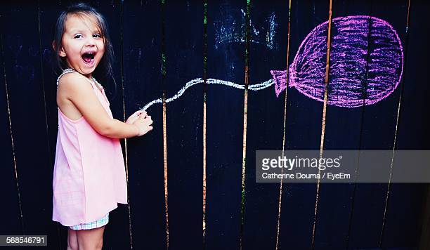 Optical Illusion Of Happy Cute Girl Holding Balloon Drawn On Wooden Wall