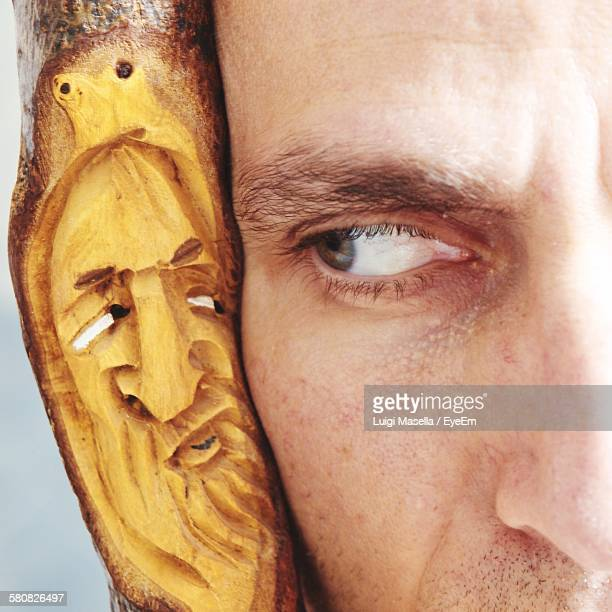 Optical Illusion Of Man Looking At Carved Wooden Stick