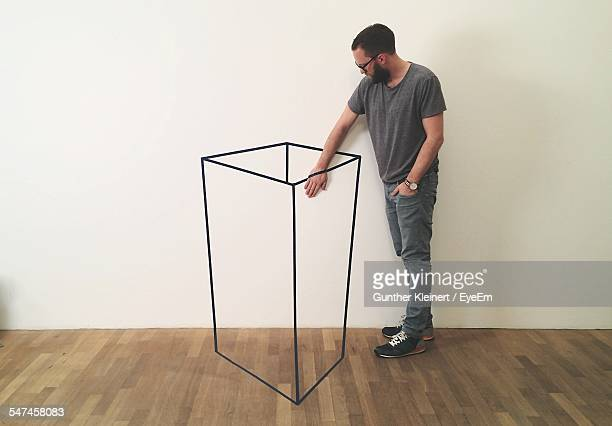 Optical Illusion Of Mid Adult Man Inserting Hand In Container Against White Wall