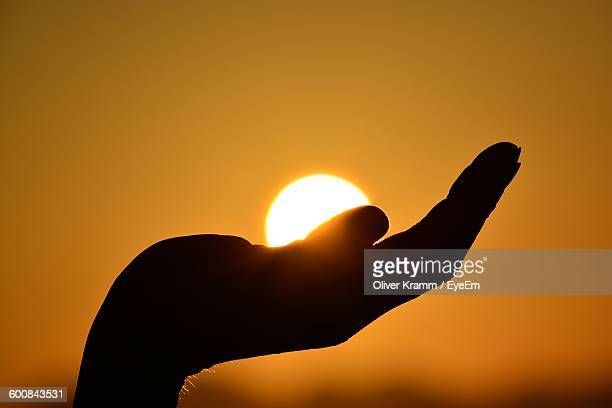 Optical Illusion Of Silhouette Hand Holding Sun Against Sky During Sunset