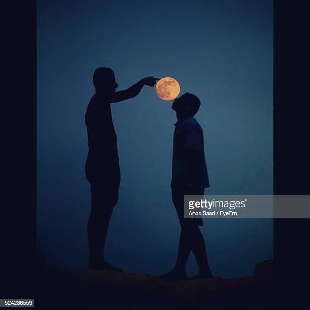 Optical Illusion of Silhouette Men Touching Full Moon At Night
