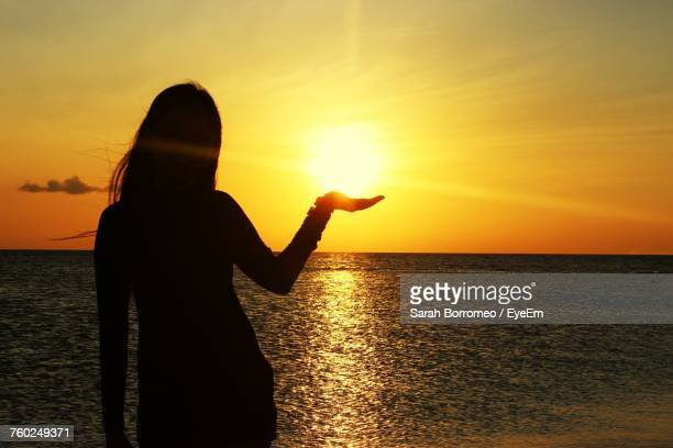 Optical Illusion Of Woman Holding Sun During Sunset