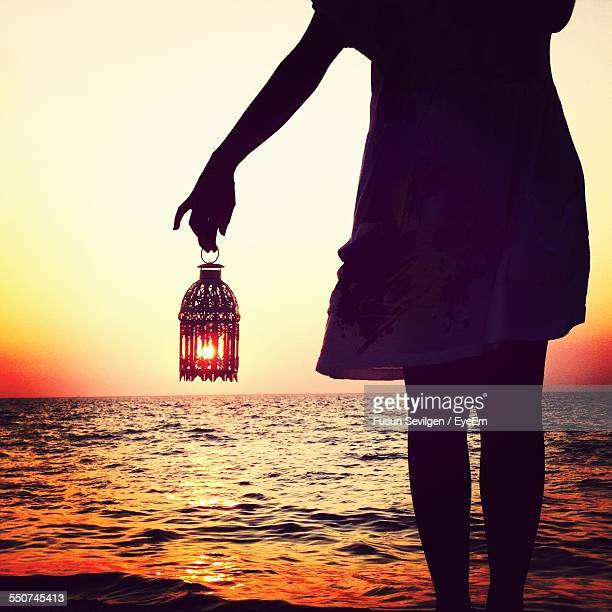 Optical Illusion Of Woman With Sun In Lantern At Beach