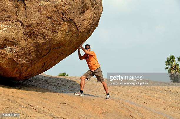 Optical Illusion Of Young Man Pushing Large Stone Against Sky