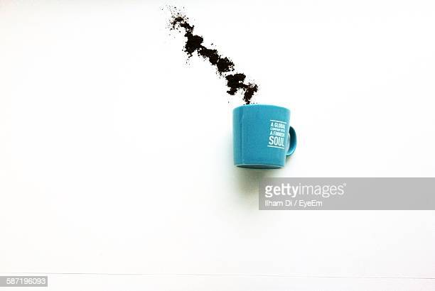 Optical Illusion On Blue Coffee Cup With Ground Coffee Against White Background
