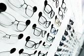 optical store, white wall of many fashionable eyeglasses