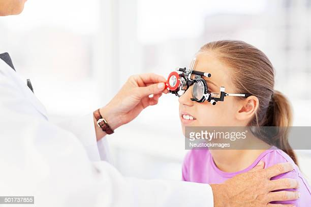 Optician Examining Girl's Vision In Clinic