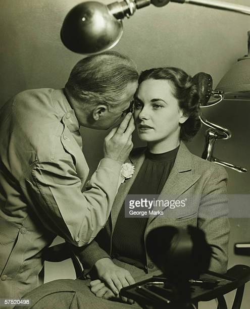 Optician examining woman's eye, (B&W)