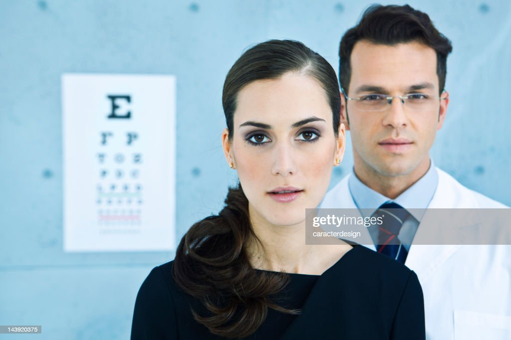 Optician in front of an eye chart : Stock Photo