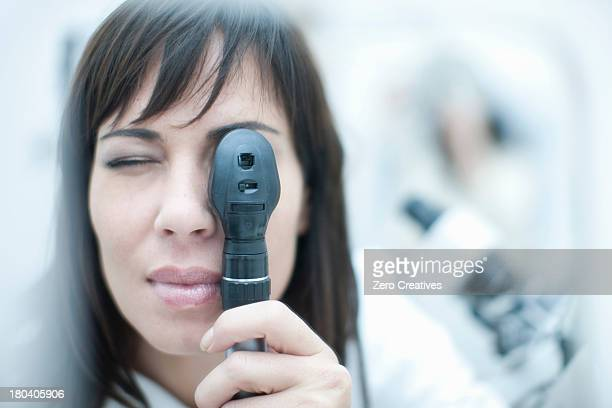 Optician looking through ophthalmoscope