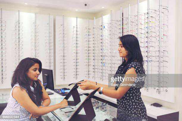Optician Showing a Spectacle to Customer