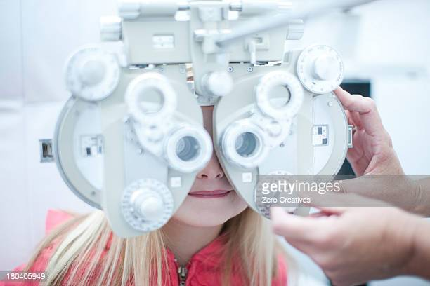 Optician testing young girl in eye clinic