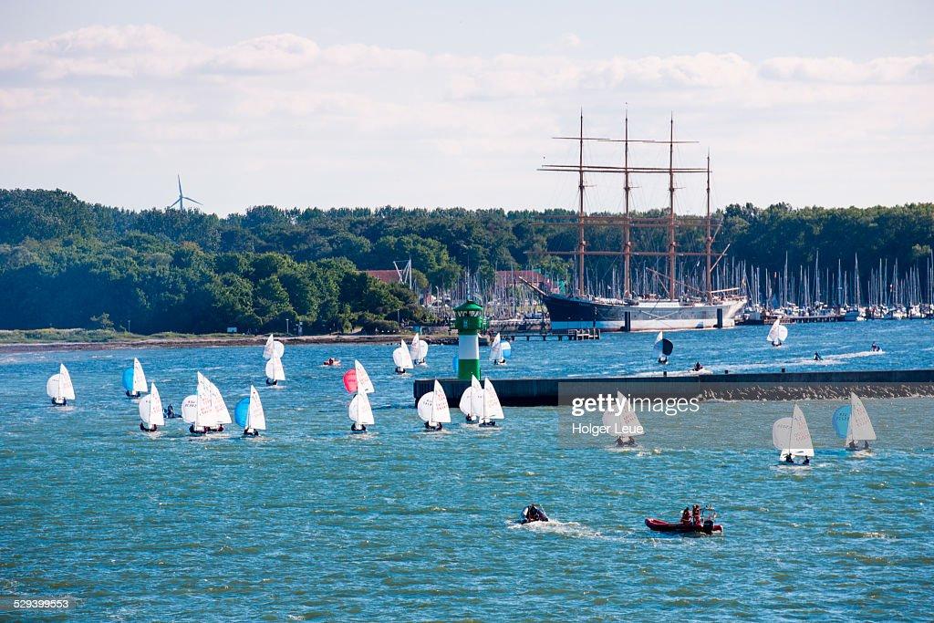 Optimist dinghy sailboats and tall ship