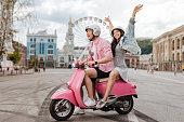 Funny ride. Joyful charming man conducting motorbike and woman putting hands up