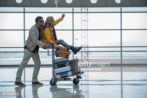 Optimistic male and female are walking to departure area : Stock Photo