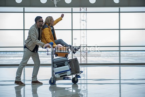 Optimistic male and female are walking to departure area : Foto de stock