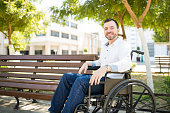 Portrait of a happy young man sitting on a wheelchair and feeling optimistic about his condition