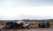 Optimus' French driver Romain Dumas and codriver Francois Borsotto are pushed out from the mud during the Stage 7 of the Dakar 2015 between Iquique...