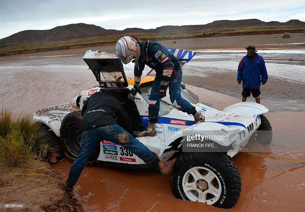 Optimus' French driver <a gi-track='captionPersonalityLinkClicked' href=/galleries/search?phrase=Romain+Dumas&family=editorial&specificpeople=805197 ng-click='$event.stopPropagation()'>Romain Dumas</a> and co-driver Francois Borsotto receive help during the Stage 7 of the Dakar 2015 between Iquique and Uyuni, Bolivia, on January 10, 2015.