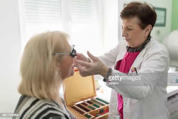 Optometrist adjusting test frame for patient