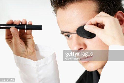Optometrist examining a young man's eye : Foto de stock