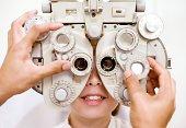 Optometrist (optician) examining eye of woman
