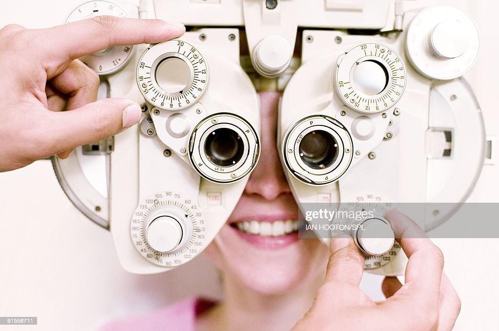 Optometrist (optician) examining eye of woman : Stock Photo