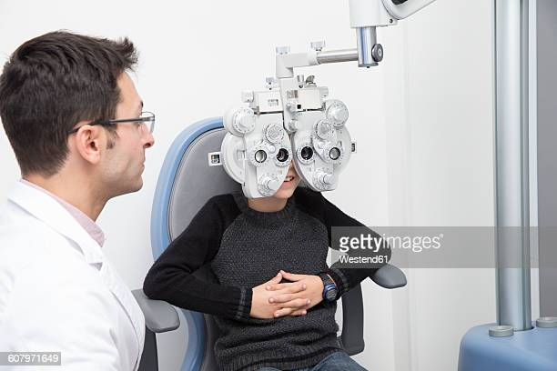 Optometrist examining eyesight of boy