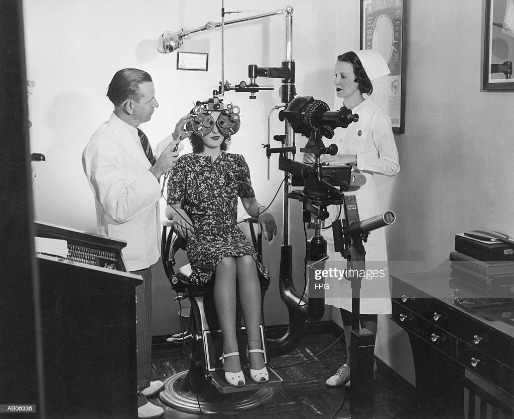 Optometrist examining woman's eyes (B&W) : Stock Photo