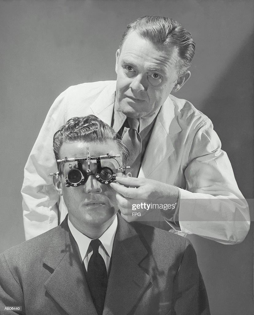 Optometrist giving man eye examination (B&W) : Stock Photo