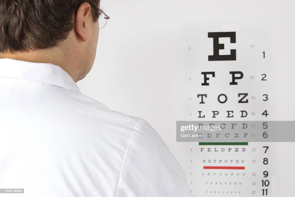 Optometrist looking at an eye chart : Stock Photo