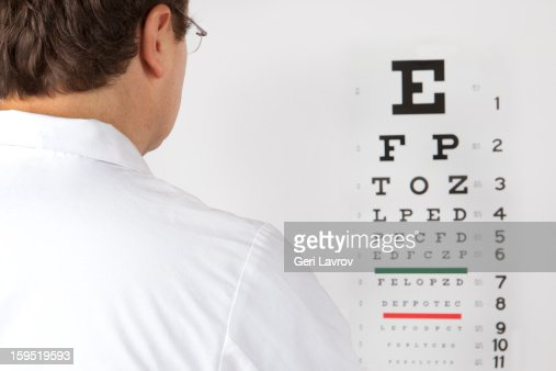 Optometrist looking at an eye chart : Stock Photo