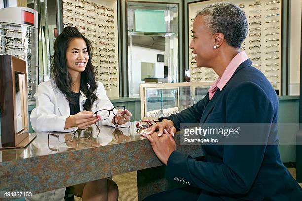 Optometrist talking to patient in office