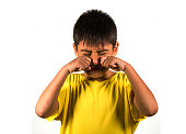 7 or 8 years old male child crying helpless and sad isolated on white background wearing yellow t-shirt in kid scolded and nagged or schoolboy bullied and abused by classmates